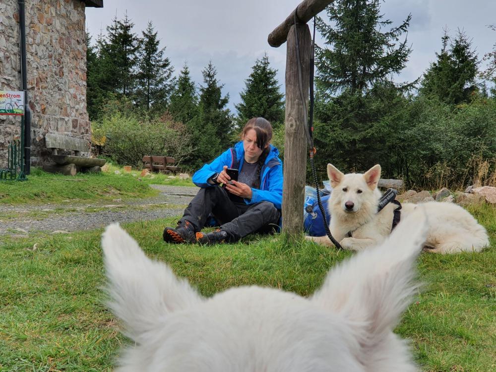 Pause an der Hanskühnenburg: Patricia und Dragon sitzen auf dem Boden und entspannen.
